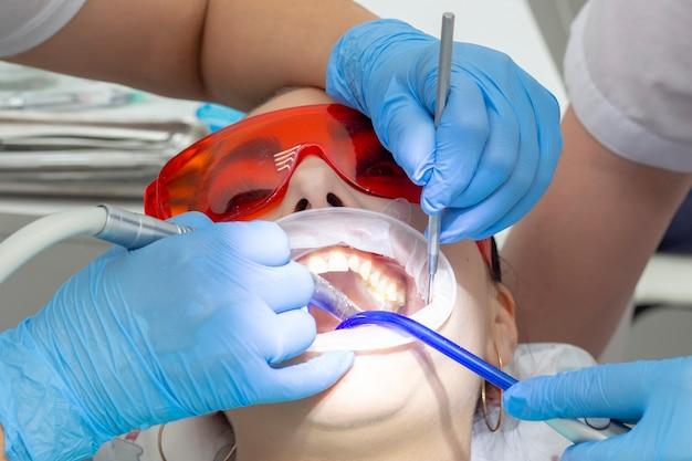 Пациентка на приеме у стоматолога. лечение кариозного зуба. девушка лежит на стоматологическом кресле с открытым ртом. дантист и его ассистент лечат зуб