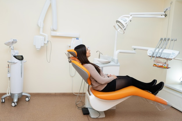 Girl patient awaiting a doctor in a chair at the dentist.