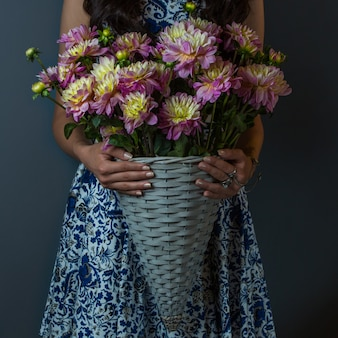 Girl in pattern dress holding a bouquet of carnations