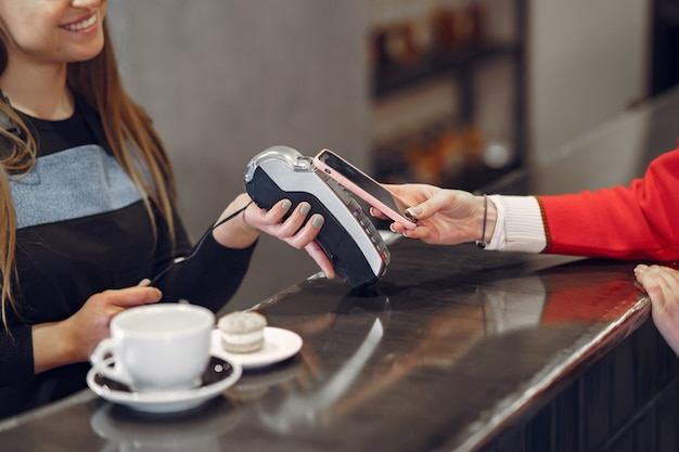 Girl paying for her latte with a smartphone by contactless pay pass technology