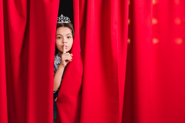 Girl peeking from red curtain making silent gesture