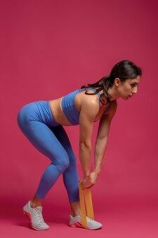 Девушка выполняет становую тягу с эспандером на бордовой поверхности