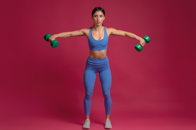 Girl performing dumbbell lateral raise on maroon wall