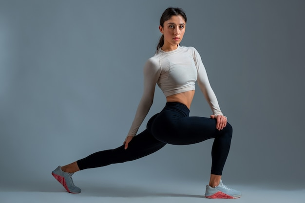 Girl performing forward lunge with body twist on grey wall