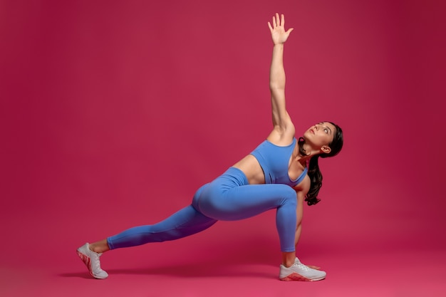 Girl performing forward lunge with hand upward on maroon surface