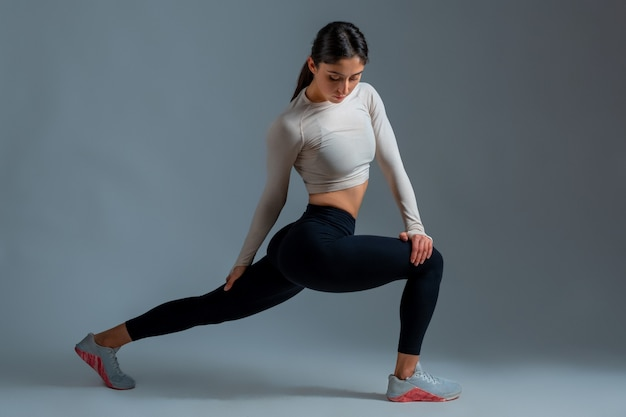 Girl performing lunges with body twists on grey wall