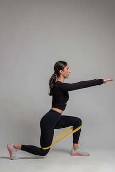 Girl performing lunges with resistance band on grey wall