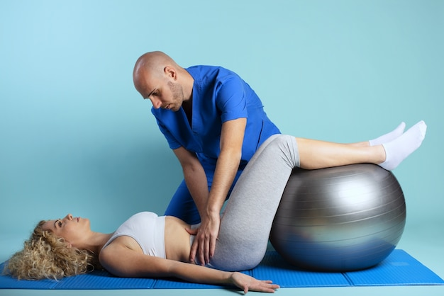 Girl performs exercises with a physiotherapist. cyan wall