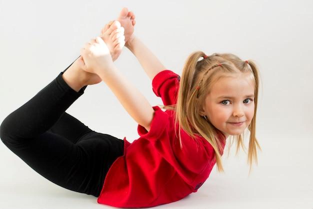 소녀는 체조 운동, 활동적인 아이를 수행하고 즐거움과 미소에 참여합니다.