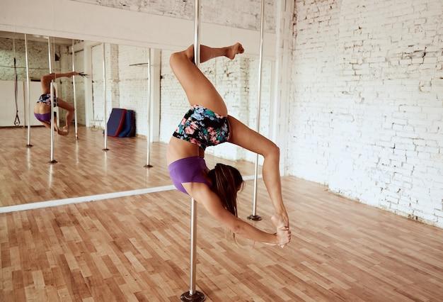 Девушка исполняет танцы на полюсе в студии с белой кирпичной стеной