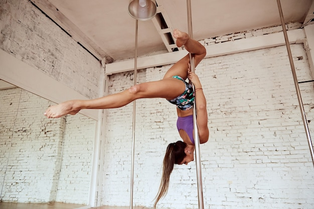 Girl performs pole dance in the studio with white brick wall
