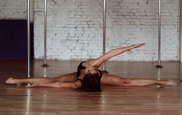 Girl performs stretching doing a leg split on the floor before pole dance training