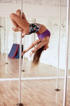 Girl performs yoga in the pole dance studio