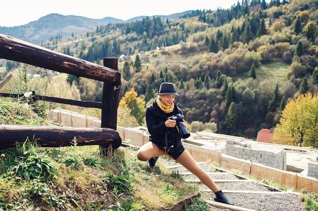 Girl photographer looks at camera on mountain in autumn.