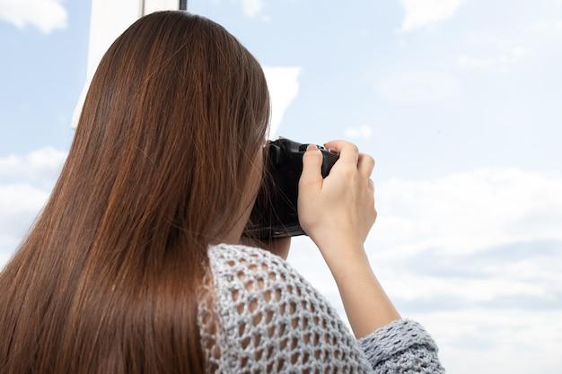 女の子の写真家は窓から風景を撮ります