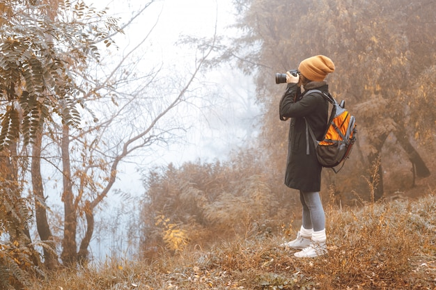 Girl photographer takes pictures of autumn nature.