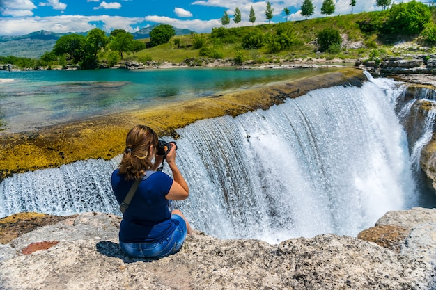 A girl photographer takes pictures of the niagara falls in montenegro.