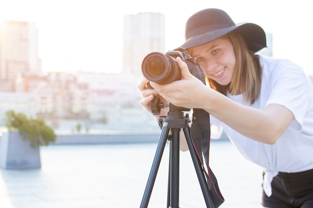 Девушка фотограф с камерой и штативом