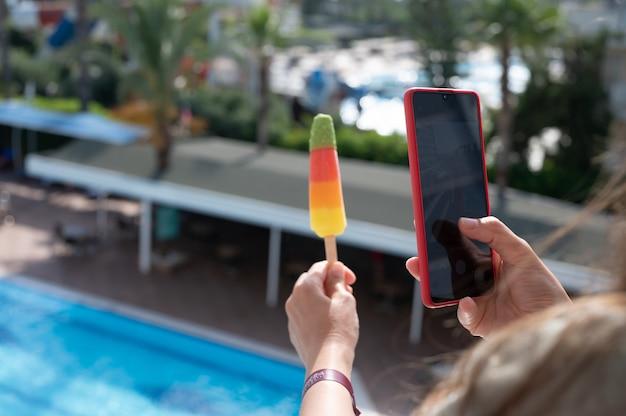 電話でアイスクリームを撮影している女の子。