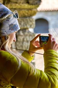 Girl photographs the landmark on a mobile phone fortress oreshek