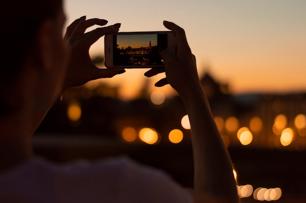 Девушка фотографирует ночные огни флоренции.