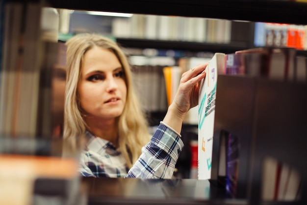 Girl picking book in library