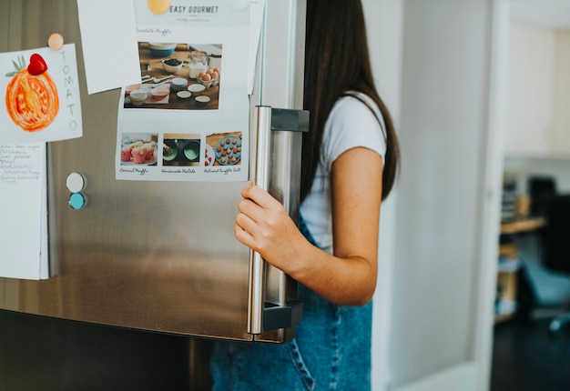 Girl picking something to eat out of the fridge