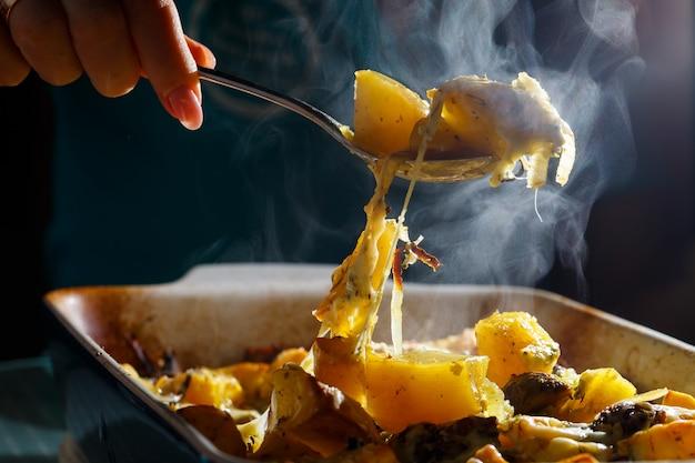 女の子はきのことチーズと一緒にベイクドポテトをスプーン一杯拾います