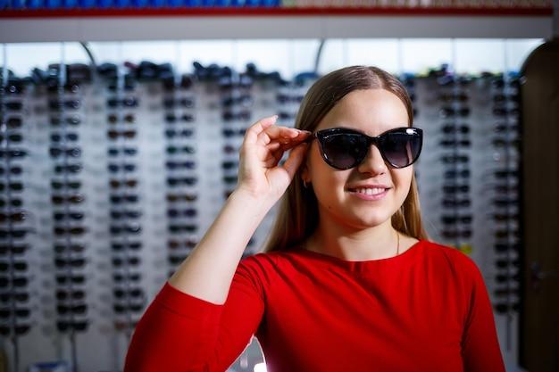 소녀는 선글라스를 선택합니다. 안경점. 시력 교정. 안경 스탠드