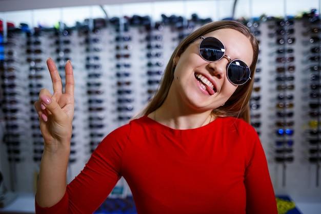 Девушка поднимает солнцезащитные очки. магазин очков. коррекция зрения. подставка для очков