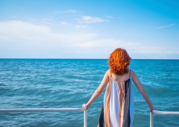 Behind girl on pier.