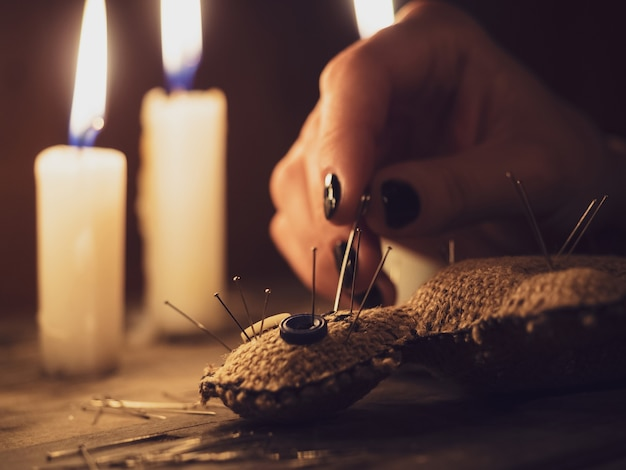 A girl pierces a voodoo doll with needles, closeup. esoteric and occult rituals on a wooden table in a dark room with many candles.