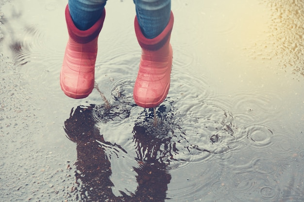 The girl in pink boots jumping in puddles after rain outdoors.