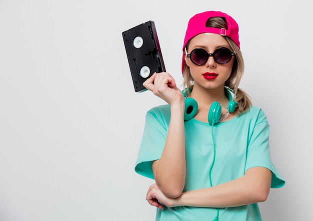 Girl in pink cap and blue t-shirt with vhs cassette