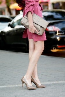 A girl in a pink cloak with bare legs and beige shoes posing on the street against the background of the city. in her hands she holds a beige clutch. in the photo, the girl is below the belt.