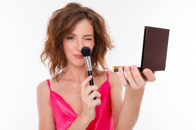 A girl in a pink dress dusts the nose with a makeup brush and holds a mirror