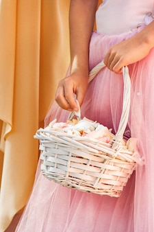 Girl in a pink dress holds a white wicker basket with rose petals. wedding ceremony