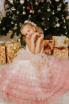 Girl in a pink dress near the christmas tree and boxes with gifts