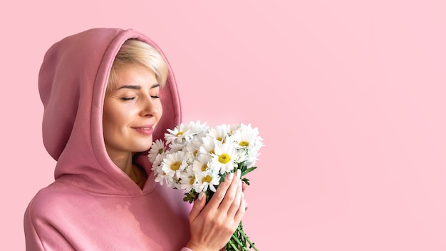 A girl in a pink hoodie with white daisies on a pink background closed her eyes to enjoy the fragrance