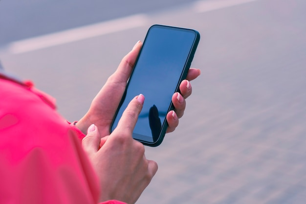 Girl in a pink jacket holds a smartphone in her hands.
