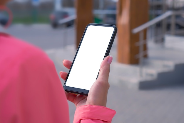 Girl in a pink jacket holds a smartphone mockup with white screen in hands. mock-up technology.