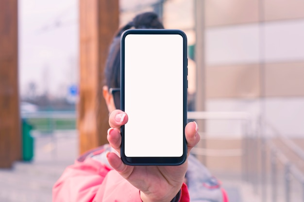 Girl in a pink jacket holds a smartphone mockup with white screen in hands