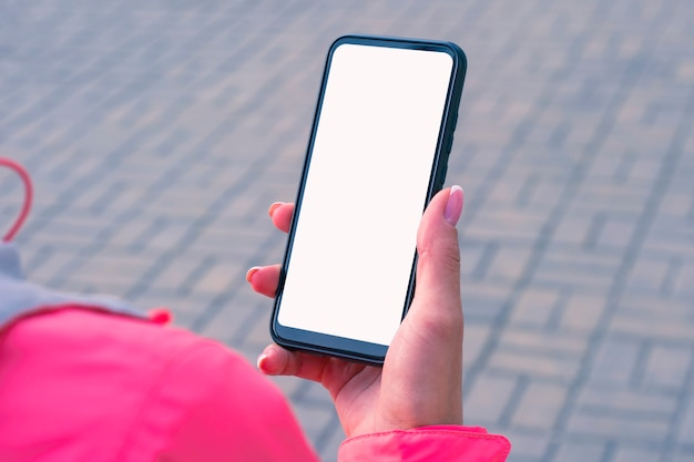 Girl in a pink jacket holds a smartphone mockup with white screen in her hands.
