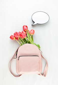 Girl pink lether back pack with red tulips and speech bubble light box.