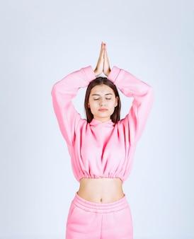 Girl in pink pajamas doing meditation