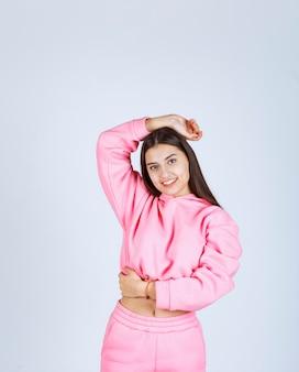 Ragazza in pigiama rosa che dà pose felici e seducenti