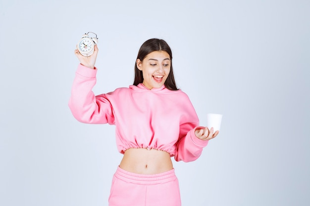 Girl in pink pajamas holding an alarm clock and a cup of coffee.