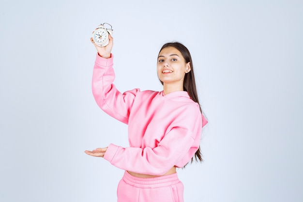 Girl in pink pajamas holding an alarm clock and promoting it as a product.
