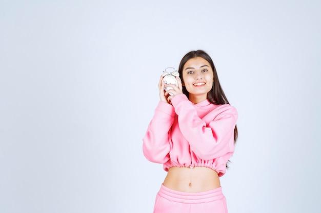 Ragazza in pigiama rosa che tiene una sveglia e la promuove come prodotto.