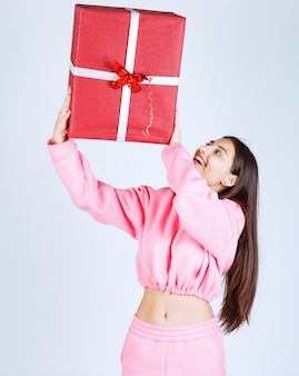 Ragazza in pigiama rosa che tiene una grande confezione regalo rossa sopra la sua testa.